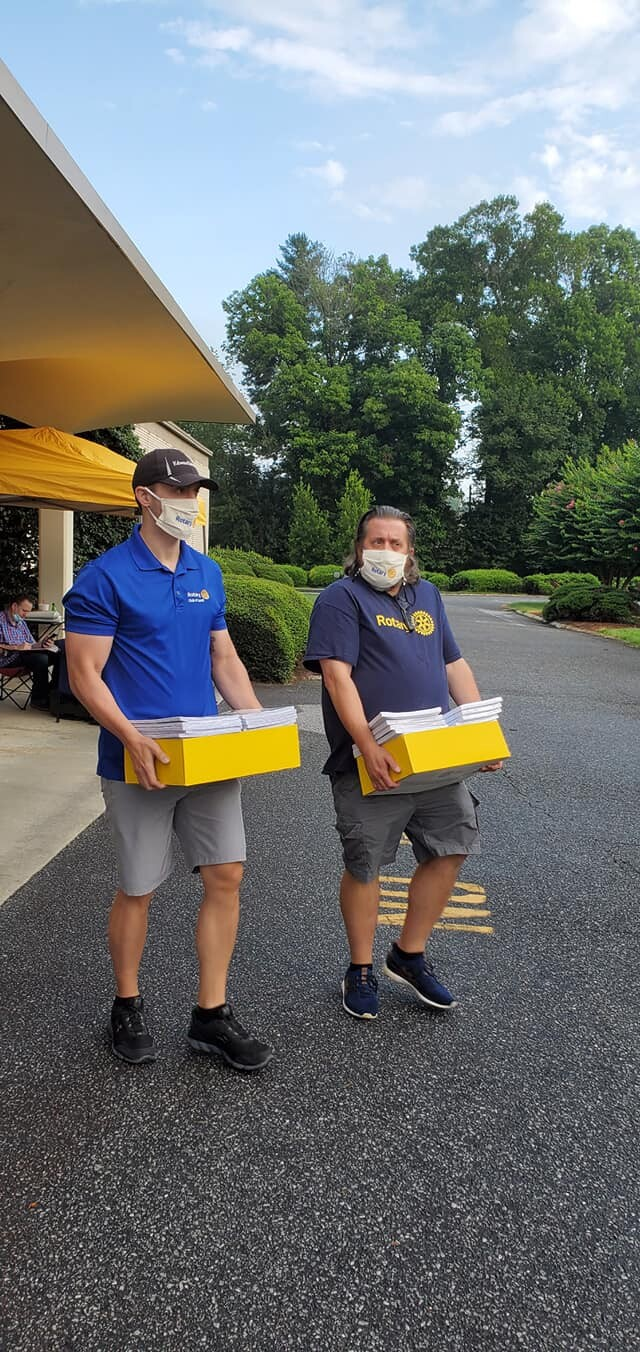 Two Rotarians carrying school supplies, wearing masks.